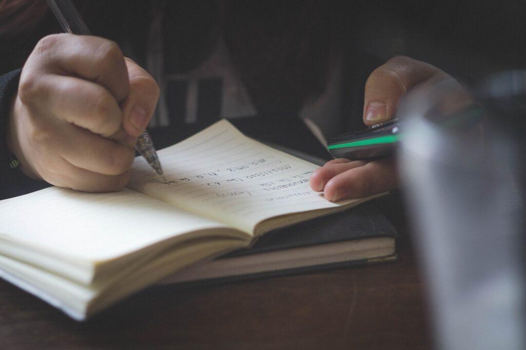 Imagem que contém uma pessoa escrevendo no caderno para ilustrar o texto sobre cursos online gratuitos sobre investimentos