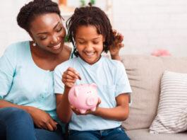 mãe e filha colocando moeda em porquinho