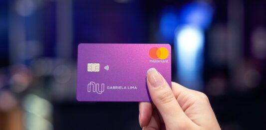 Mão segurando um cartão do Nubank