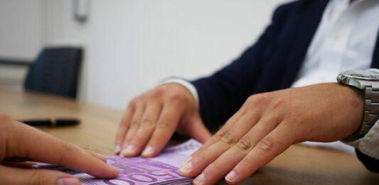 uma pessoa entrega notas de dinheiro a outra