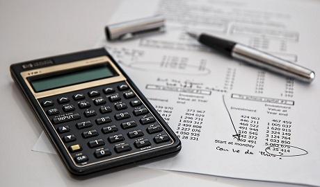 imagem contém uma calculadora e canela por cima de papéis