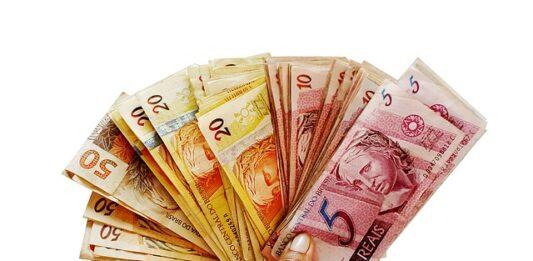 imagem de uma mão segurando várias notas de dinheiro
