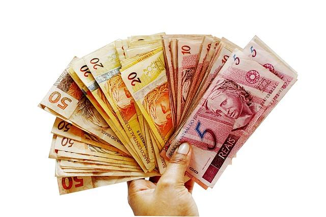 Uma mão de pessoa branca segurando diversas notas de cinquenta reais, vinte reais, dez reais e cinco reais para ilustrar o texto sobre calendário do auxílio emergencial