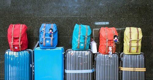 Fileira com cinco malas com uma mocihila em cima de cada uma