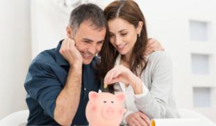 casal sorrindo e depositando moeda no cofre de porquinho rosa
