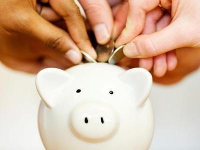 mãos abastecendo cofre de moedas para poupança