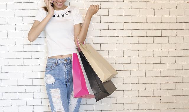 mulher falando ao celular e segurando várias sacolas de compras