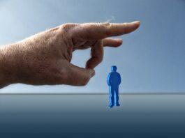 uma mão dando peteleco em uma pessoa