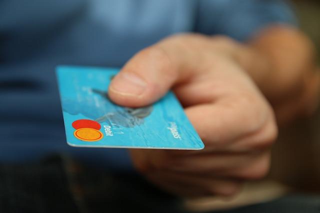 imagem de uma pessoa segurando um cartão mastercard na cor azul