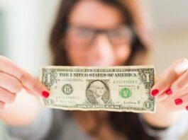 mulher segurando uma nota de dólar com as duas mãos