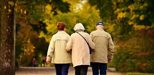 imagem de três idosos andando pela praça
