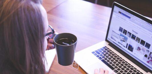 profissional freelancer de frente para o notebook segurando uma caneca