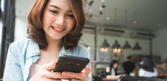 Mulher procurando por cupons de desconto na internet pelo celular