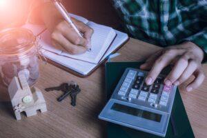 Homem calculando décimo terceiro usando calculadora e caderno