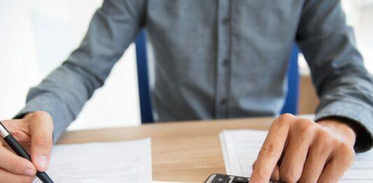 Pessoa usando uma calculadora para verificar seus rendimentos