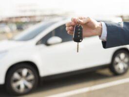 carro branco com uma mão segurando a chave do carro
