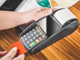 pessoa segurando máquina de cartão de crédito