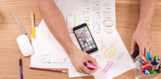imagem vista de cima com diversos papéis, um celular e tela de um computador