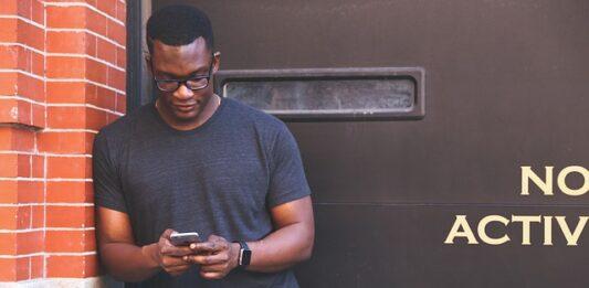 Homem encostado na parede mexendo no celular