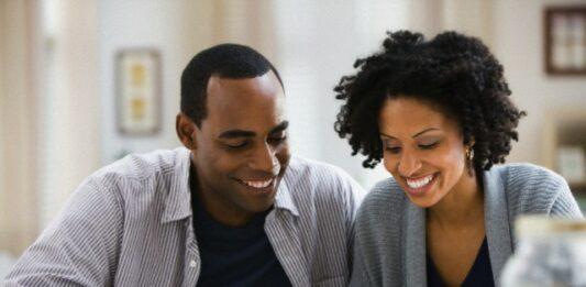 Homem e mulher sentados a mesa contam notas de dinheiro