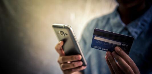 Homem usando celular com cartão de crédito em outra mão