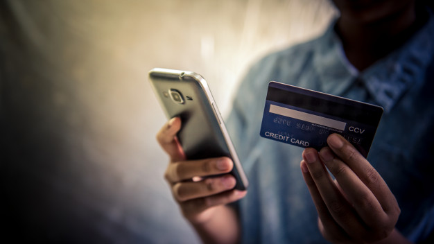 Pessoa usando celular com cartão de crédito na mão