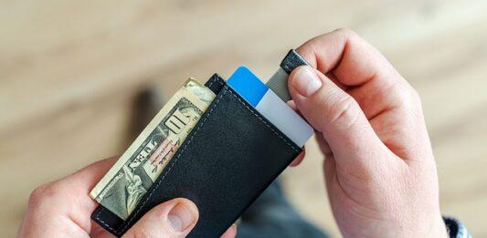 pessoa retirando cartão da conta digital de dentro da carteira preta