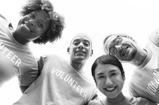 quatro pessoas abraçadas realizando trabalho voluntário