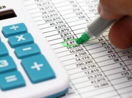 pessoa com folha e calculadora realizando o cálculo da rescisão trabalhista