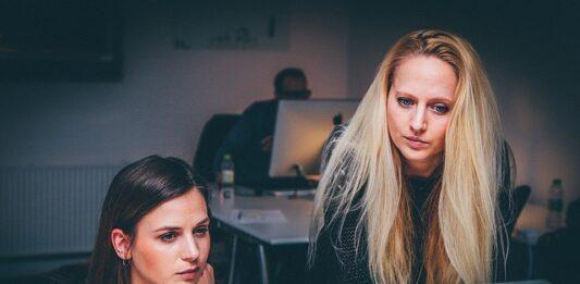 duas mulheres olhando a tela de um computador