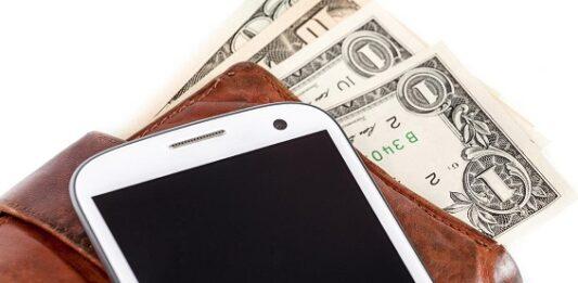 imagem de um celular em cima de uma carteira com notas de dinheiro