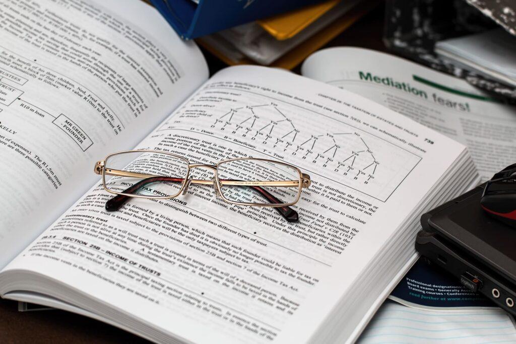 imagem de um livro aberto com óculos em cima