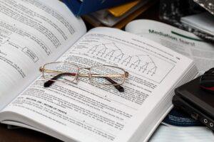Óculos em cima de um livro aberto