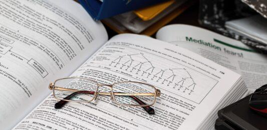 Um livro para investidores aberto com óculos em cima
