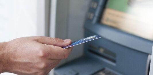 pessoa usando o cartão em um caixa eletrônico