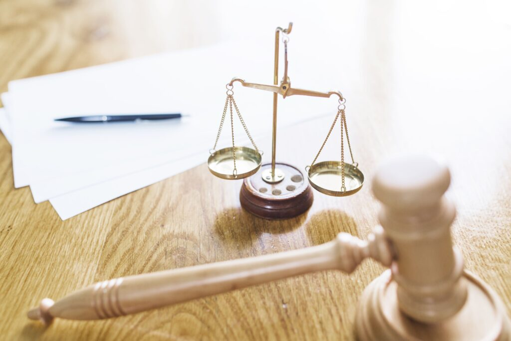 um papel com a caneta acima, uma balança e uma martelo, objetos típicos da justiça em uma mesa