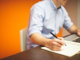 imagem de um homem sentado escrevendo e fazendo contas