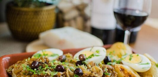 Prato com bacalhau e ovos em uma travessa na mesa, com taça de vinho