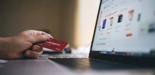 Pessoa segurando cartão de crédito e acessando loja virtual