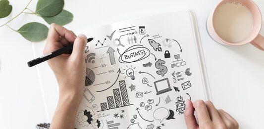Mão masculina desenha ideias de negócios no papel
