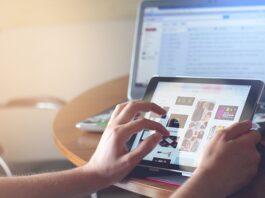 pessoa utilizando tablet com tela de computador de fundo