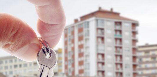 Mão de uma pessoa segurando as chaves com vários prédios ao fundo