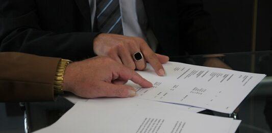 Duas pessoas analisando contrato