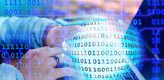 imagem de uma pessoa mexendo no notebook com vários códigos na tela