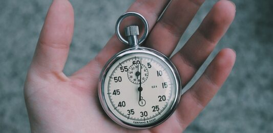 Uma mão segurando um relógio de bolso