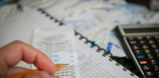 mão com caneta anotando na nota fiscal que está em cima de um caderno