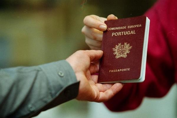 Duas pessoas segurando um passaporte de Portugal