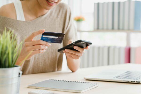 mulher com um cartão de crédito e um celular na mão