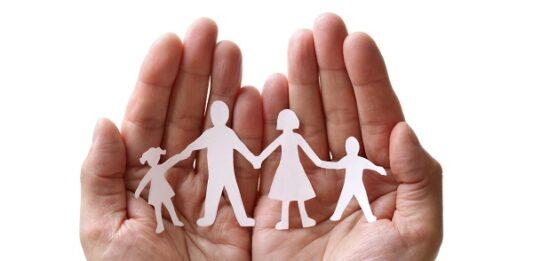 Duas mãos segurando um recorte de papel representando família de 4 pessoas