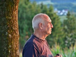 Homem idoso na natureza segurando um binóculo